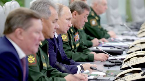Russian President Vladimir Putin (centre) watches a video link of a successful test launch of the Avangard intercontinental strategic missile, with Russian Defence Minister Sergei Shoigu on his right and Head of the Russian Armed Forces Army General Valery Gerasimov on his left.