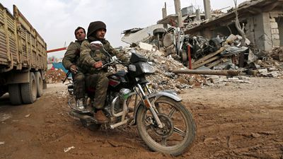 Fighters in a motorbike cruise around destroyed buildings.