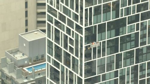 The strong winds left two window cleaners dangling 34 storeys above the ground on Spring Street.