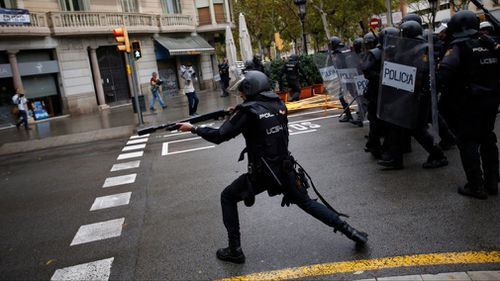Spanish riot police shoots rubber bullet straight to people trying to reach a voting site at a school assigned to be a polling station by the Catalan government. (AP)