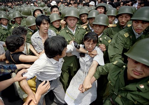 A young woman is caught between civilians and Chinese soldiers, who were trying to remove her from an assembly near the Great Hall of the People in Beijing.