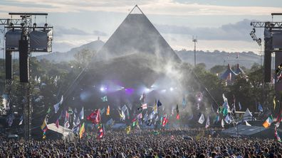 People gather in front of the Pyramid Stage at Worthy Farm in Pilton on June 25, 2017 near Glastonbury, England.