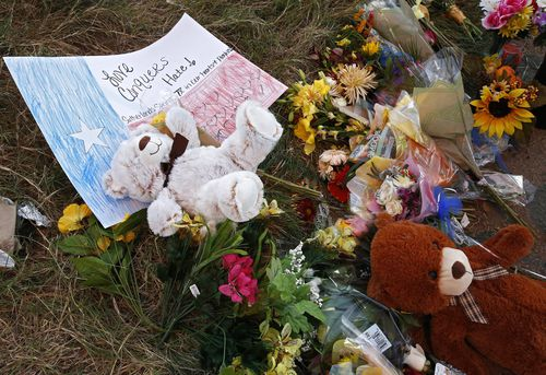 Flowers and stuffed bears lie on the ground down the street from the church. (AAP)