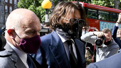 Johnny Depp, right, wearing a protective mask arrives at the Royal Court of Justice, in London, Tuesday, July 7, 2020.