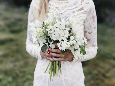 Bride standing in white dress holding flowers.