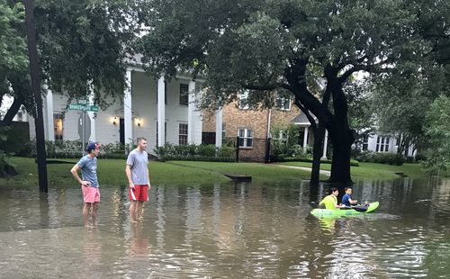 Australian BHP Billiton employee David Bryant (left) and his American friend Robert Sears survey a flooded street in his Houston neighbourhood. (AAP)
