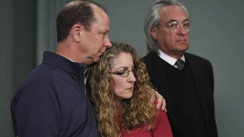 Jim Piazza and Evelyn Piazza hold one another as they listen to District Attorney Stacy Parks Miller. (AAP)