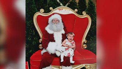 Baby signs for help in Santa photo