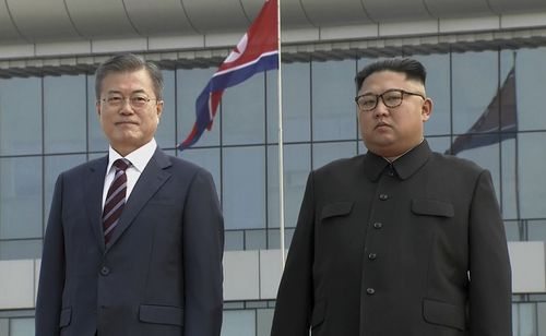 South Korean President Moon Jae-in, left, poses with North Korean leader Kim Jong-un for a photo on the podium upon arrival in Pyongyang.