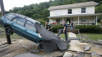 Men survey the damage to a car in White Sulphur Springs. (AAP)