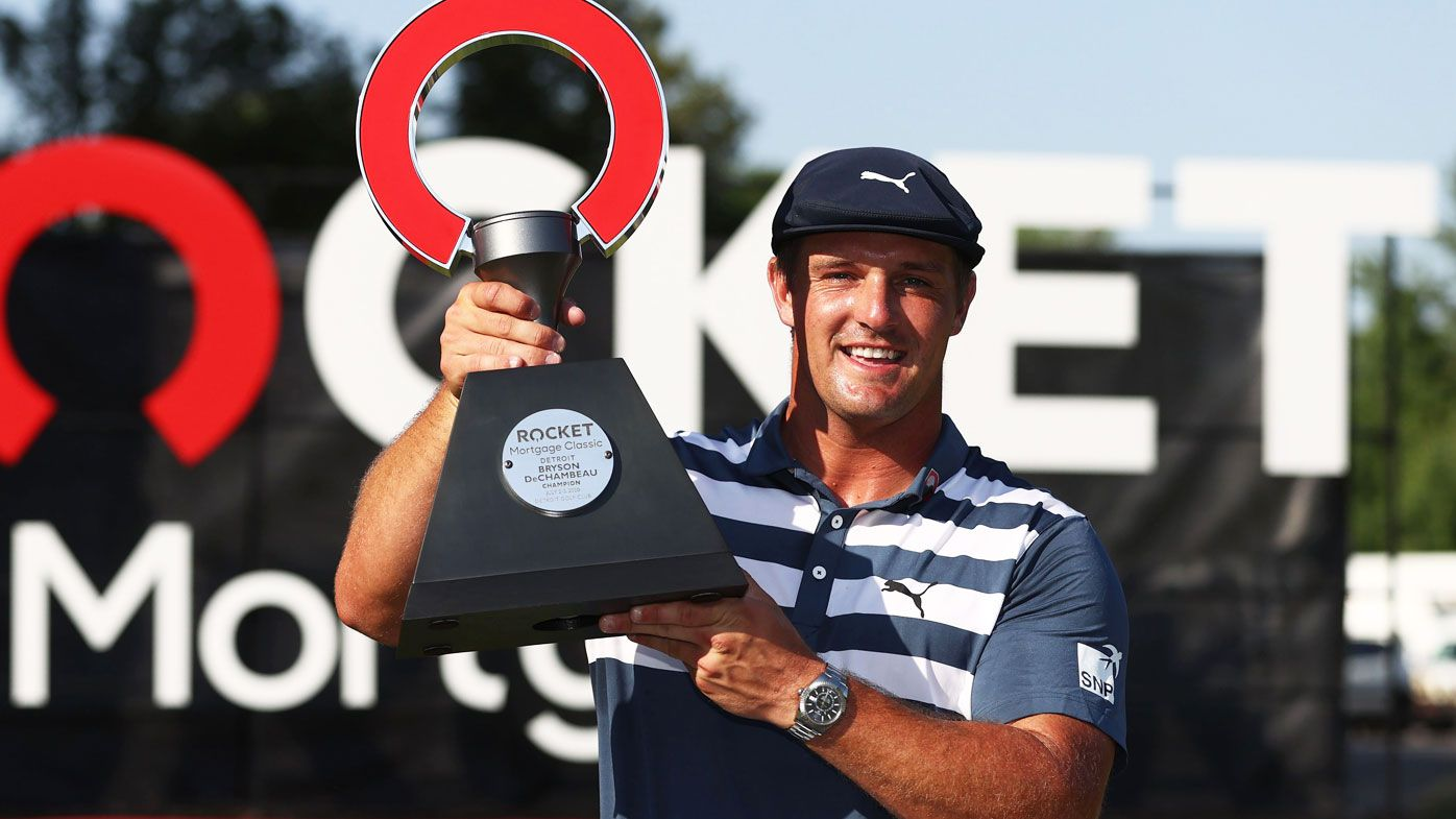 Bryson DeChambeau of the United States celebrates with the trophy after winning during the final round of the Rocket Mortgage Classic