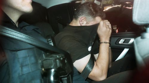 Fugitive Jonathan Dick is driven into Police Headquarters after his arrest in Melbourne.