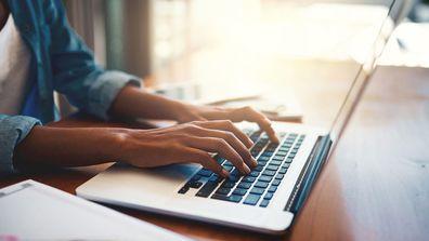 woman typing on laptop.