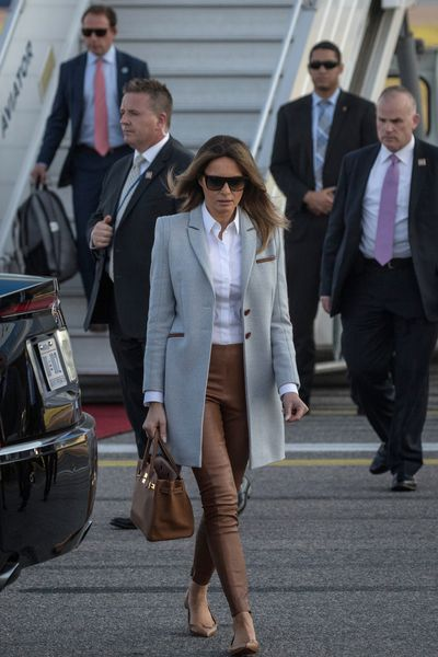 Melania Trump in a grey coat from Isoude and leather pants from Ralph Lauren