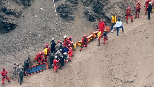 Rescue workers carry a victim on a stretcher. Photo: AAP