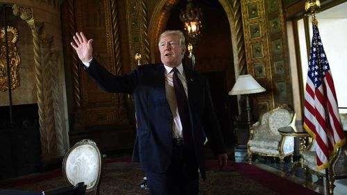 President Donald Trump waves as he leaves the room following his talk with reporters and troops via teleconference from his Mar-a-Lago estate in Palm Beach, Florida.