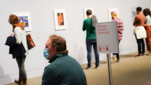 Visitors wearing protective masks observe COVID-19 prevention protocols as they browse the Jacob Lawrence: The American Struggle exhibition at the Metropolitan Museum of Art, Saturday, Oct. 17, 2020, in New York. (AP Photo/John Minchillo)