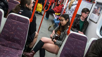 Not content with drawing looks for her pants-free outfit this woman strums a guitar to make sure no one misses her.