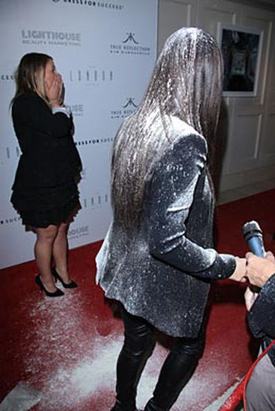A female onlooker dumps a bag of flour over the star on the red carpet.