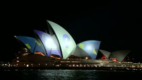 At 7.40pm when the famous sails were first lit up, people lining the building's forecourt also began to shine beams of light from torches onto the images in the hopes of obscuring the message.