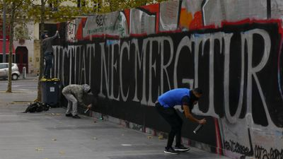 "Three graffiti artists work on a Latin mural that reads: ""tossed but not sunk"". (Jack Hawke, 9News.com.au)"