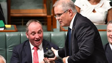 Scott Morrison hands Barnaby Joyce a lump of coal in parliament.