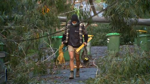 A man carrying tools walks through a street ravaged by wild weather that struck parts of Victoria.