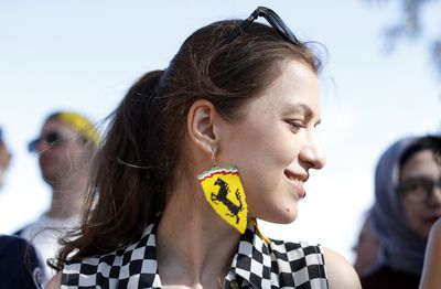 A woman with the Ferrari stable proudly shows off her Prancing Stallion earrings at the Melbourne Grand Prix. (AAP)