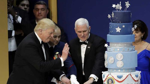 Image: Getty. Trump cuts the controversial inauguration cake during the Armed Services Inaugural Ball in Washington, D.C., on Friday, Jan. 20, 2017