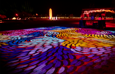 Artist Daphne Marks' work 'Yalka Tjukurrpa - Bush Onion Dreaming' projected onto the floor in a rainbow display.