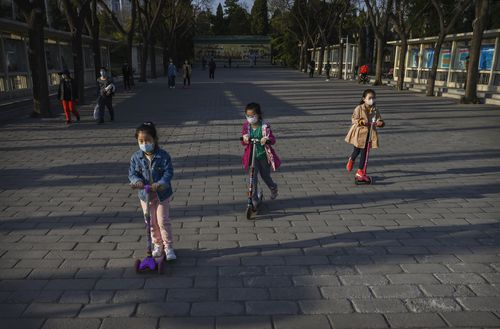 Chinese girls wear protective masks as they ride scooters at Ritan Park on March 22, 2020 in Beijing.
