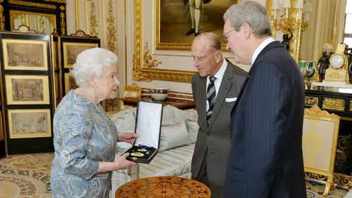 Queen Elizabeth talks with the Australian High Commissioner Alexander Downer as she prepares to present Britain's Prince Philip with the Insignia of a Knight of the Order of Australia. (AAP)