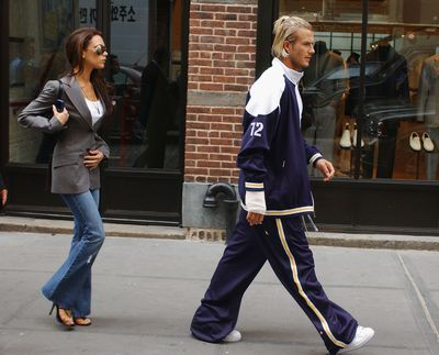 <p>Full Flare</p> <p>Victoria's flared denim jeans, bejeweled stilettos and floor-length extensions take a backseat to David's over-sized tracksuit and bleached ponytail in New York 2002.</p>