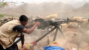 A member of Yemeni government forces fires a heavy machine gun during an offensive against Houthi positions on the outskirts of the western port city of Hodeidah, Yemen. (AAP)