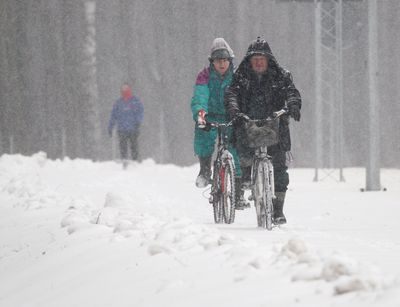 Poland: People attempt riding bikes through the dense snow
