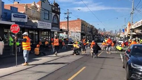 Construction workers block off Sydney Road in Brunswick as part of their protest.