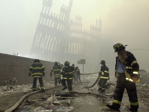 With the skeleton of the World Trade Centre in the background, firefighters work amid debris on Cortlandt St after the terrorist attacks.