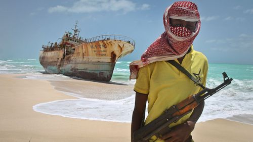A file photo from 2012 shows a masked Somali pirate near a Taiwanese fishing vessel that washed up on shore after the pirates were paid a ransom and released the crew in Hobyo, Somalia.