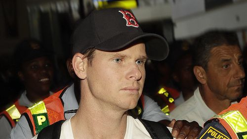 Smith was surrounded by security and heckled as he left Johannesburg to fly home. (AAP)
