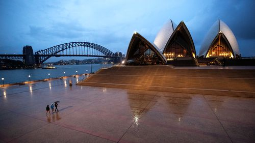 People walk on the forecourt of the Sydney Opera House. Sydney is deserted as people stay home because of the coronavirus and social distancing measures.