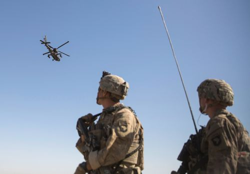 An AH-64 Apache attack helicopter flies above as US Soldiers at Task Force Iron at Bost Airfield in Afghanistan watch on.