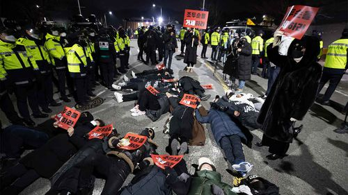 Protesters lie down on the road to oppose the release of Cho Doo-soon in front of a prison in Seoul.