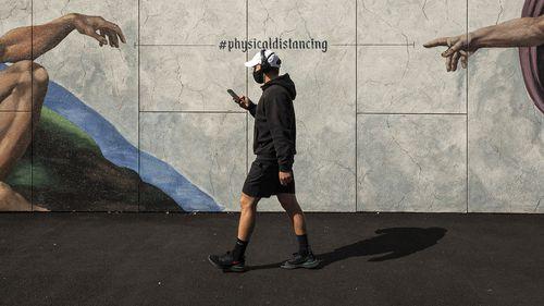 A man wearing a mask walks past street art in South Melbourne