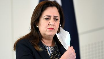 Queensland Premier Annastacia Palaszczuk takes her mask off during a press conference