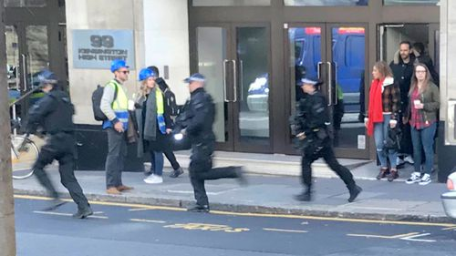 People watch as armed police officers run to the scene of an incident in central London amid reports a man with a machete has entered the Sony Music headquarters.