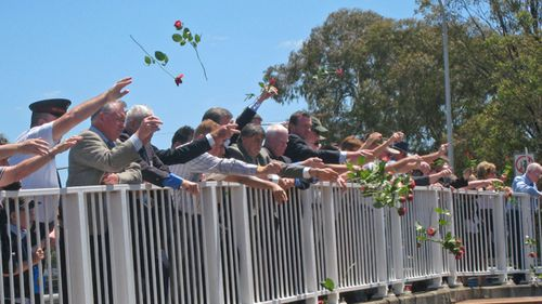 People gather at Bold Street Bridge in western Sydney for the traditional throwing of roses onto the train tracks below, as they commemorate the 32nd anniversary of the Granville Train Disaster
