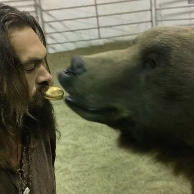 Jason Momoa lets a bear eat an oreo out of his mouth on the set of his new show, See.
