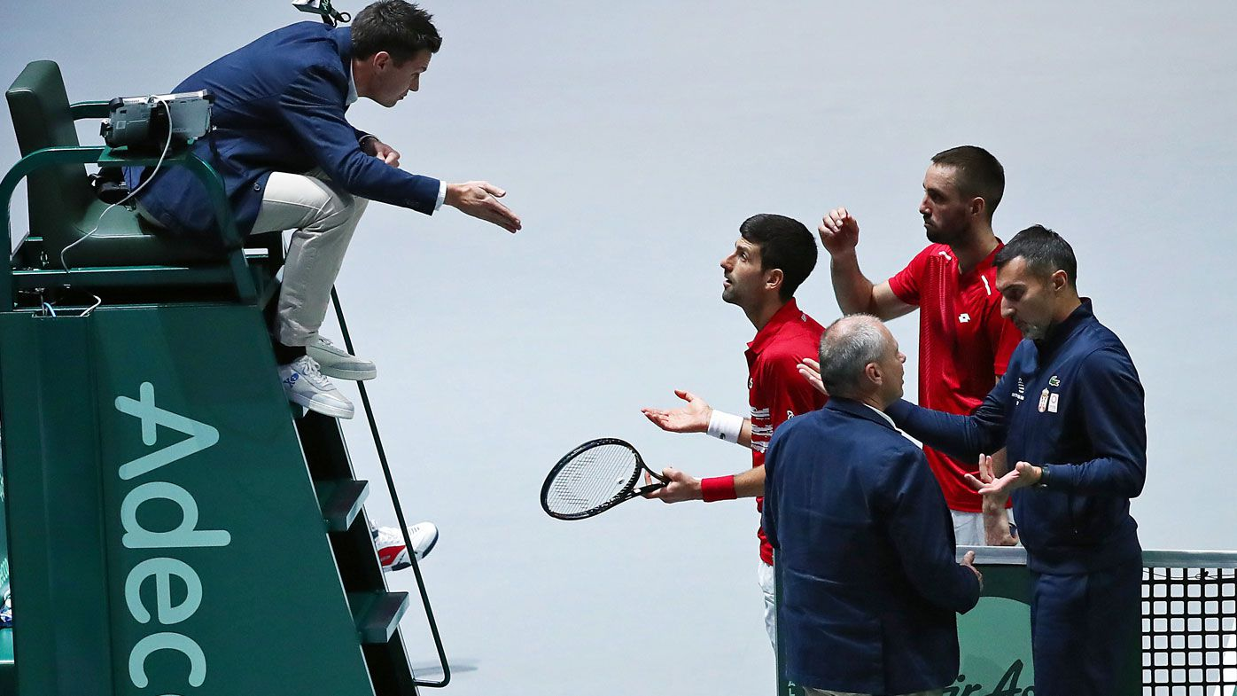 Novak Djokovic of Serbia, team mate Viktor Troicki, Coach Nenad Simic and Tournament Referee Wayne McKewen talk to the umpire during their quarter final doubles match