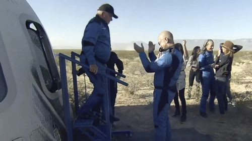An emotional William Shatner exits the Blue Origin capsule and is greeted by Jeff Bezos.