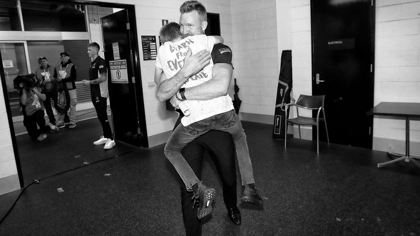 Collingwood coach Nathan Buckley embraces son after momentous AFL finals victory, tumultuous season